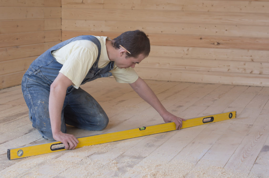 Carpenter checks the accuracy of the sub-floor horizon.