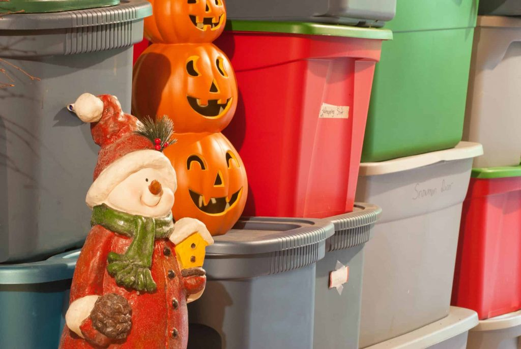 Plastic storage bins, filled with decorations for various holidays.